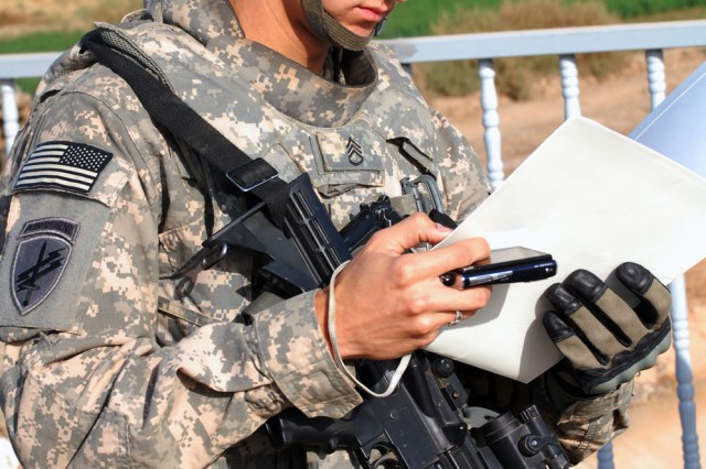 TAJI, Iraq - Cambridge, Mass. native, Staff Sgt. Carlos Madden, a civil affairs team leader assigned to 1379th Civil Affairs Company, uses a public works contract to inspect the Sheik Abdullah Bridge in Taji, Nov. 10. The bridge is a civil capacity project that offers residents of the rural area a quicker route to the nearby markets.