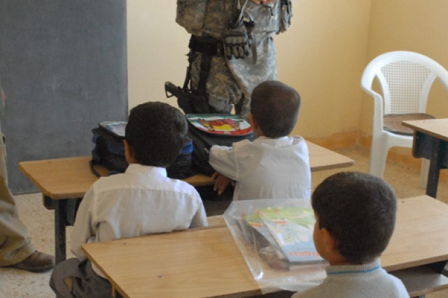 Sergeant first Class Raymond Loriaux, a team leader with the 414th Civil Affairs Company, talks to children in the school in the small village of Sarbir in Kirkuk province, Iraq, Nov. 12. Loriaux's civil affairs team helped to organize a school supply drop for these children.