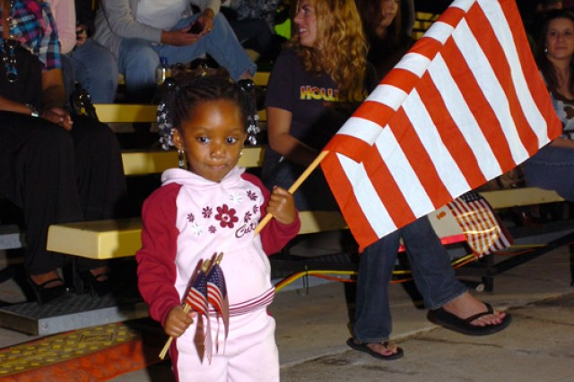 Two-year-old Takara Guice, holds one large American flag and two smaller American Flags as she waits for her father, Staff Sgt. Truman Guice, of 3rd Battalion, 8th Cavalry Regiment, 3rd Heavy Brigade Combat Team, 1st Cavalry Division, Nov. 10, at Cooper Field, in Fort Hood, Texas, during a welcome home ceremony. Approximately 300 Soldiers returned from a year-long deployment in Iraq.