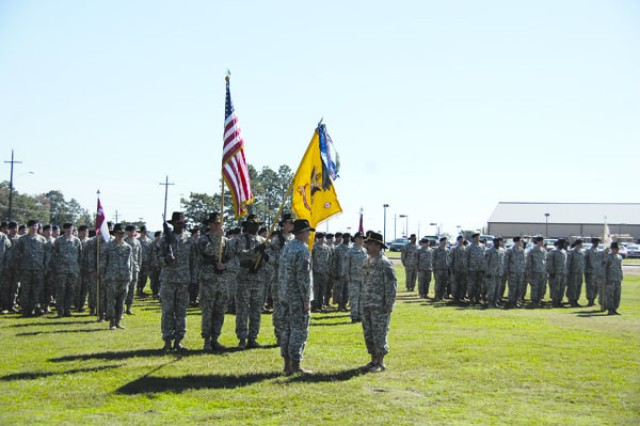 Lt. Col. Phillip Chambers, commander, 3rd Squadron, 89th Cavalry Regiment, 4th Brigade Combat Team, 10th Mountain Division (left) and Command Sgt. Maj. Ronald Semerena, command sergeant major, 3/89th, stand at attention after placing a Valorous Unit Award streamer on the unit's colors during a ceremony Nov. 6 at Mountain Field on Fort Polk.