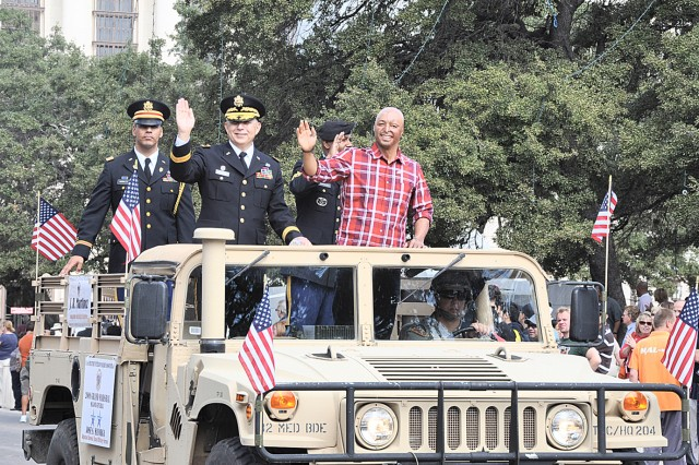 """Veterans Day Parade Grand Marshal Maj. Gen. Jose Mayorga, adjutant general, State of Texas Military Forces, with his staff, and Honorary Grand Marshal J.R. Martinez, wave to the crowd. Martinez, a wounded warrior, is now an actor in the soap opera """"All My Children."""""""