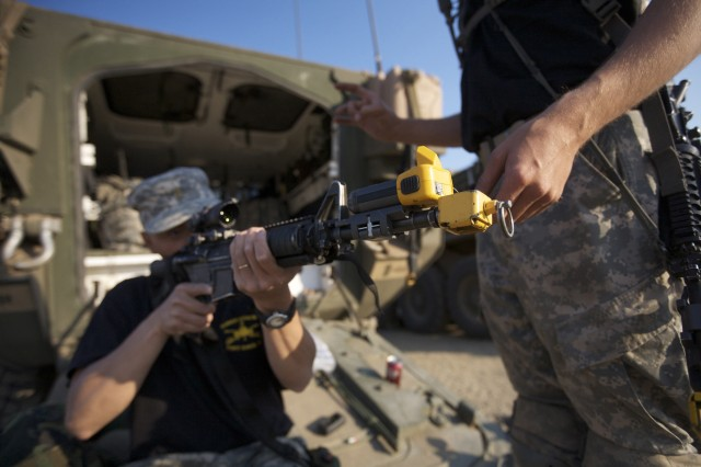 Soldiers of O Troop, 4th Squadron, 2nd Cavalry Regiment, based in Vilseck, Germany, adjust a weapon equipped with the Deployable Instrumentation Systems Europe, or DISE, before the next morning's training mission at the Babadag Training Area in eastern Romania, as part of Joint Task Force-East's third annual exercise, Sept. 24.