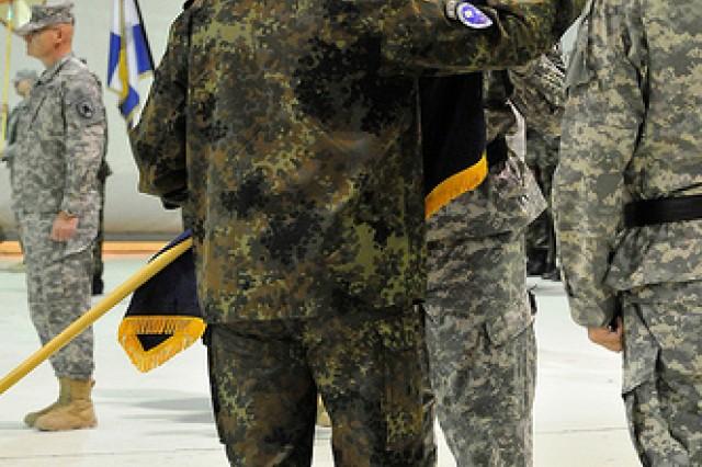 Kosovo Force Commander Lt. Gen. Markus Bentler presents KFOR 12 Multi-National Task Force-East  Commanding General Brig. Gen. Alan S. Dohrmann with the colors of MNTF-East during a transfer-of-authority ceremony at Camp Bondsteel, Kosovo, Nov. 14.