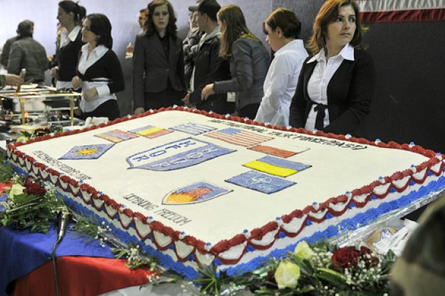 Kosovo Forces celebrate with cake after the KFOR 11 and KFOR 12 Multi-National Task Forces transfer of authority ceremony.