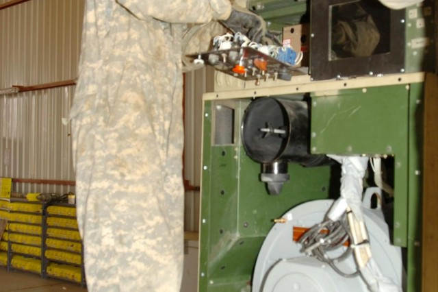 Pfc. Tammy Gallaher, power generation equipment repair specialist, Headquarters Support Company, 209th Aviation Support Battalion, 25th Combat Aviation Brigade, services a 60-kilowatt generator at Contingency Operating Base Speicher, Iraq, Oct. 30.