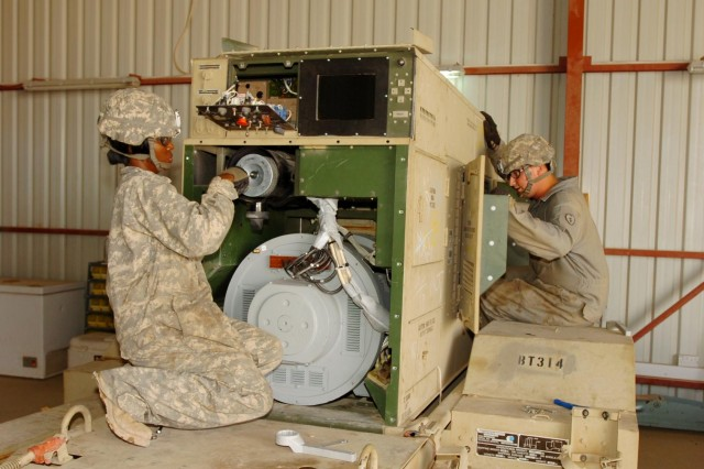 Pfc. Tammy Gallaher (left) and Spc. Michael Boyle (right), both power generation equipment repair specialists, Headquarters Support Company, 209th Aviation Support Battalion , 25th Combat Aviation Brigade, repair and service a 60-kilowatt generator at Contingency Operating Base Speicher, Iraq, Oct. 30.