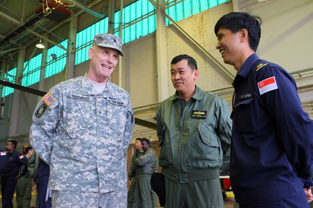 Brig. Gen. Roger Mathews, commandant of the Air Defense Artillery School, talks with Singaporean airmen in a hangar at Fort Sill's Henry Post Army Airfield Nov. 14. A 600-soldier task force of Singaporean soldiers and airmen are in Southwest Oklahoma for the three-week long Forging Sabre combined warfighter exercise with both Soldiers from Fort Sill and Oklahoma National Guard Soldiers.
