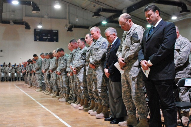 Soldiers, Airmen and civilians bow their heads in prayer during a memorial ceremony for Pvt. Francheska Velez on Forward Operating Base Warrior, Kirkuk, Iraq, Nov. 13. Pvt. Velez was killed during a shooting on Fort Hood, Texas, Nov. 5.