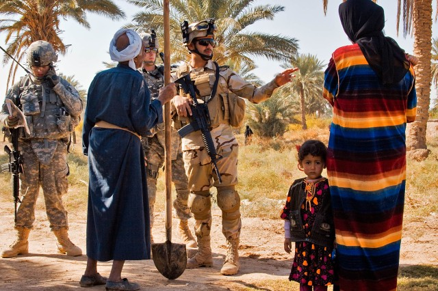 TAJI, Iraq-An Iraqi Army Soldier from the 34 IA Brigade, with support from Soldiers of 1st Air Cavalry Brigade, talks with local villagers about living conditions and any possible terrorist activities in an area north Taji, Iraq, Nov. 12.