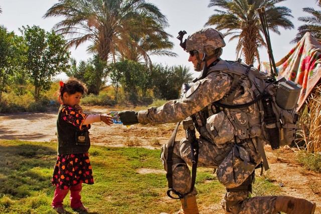 TAJI, Iraq-1st Lt. Austin Huckabee, from San Angelo, Texas, hands a small bag of candy to a young Iraqi girl during a patrol in a small village north of Taji, Iraq, Nov. 12. American Soldiers and the 34th Iraqi Army Brigade performed a joint air assault mission and patrol to check on living conditions of the small village.