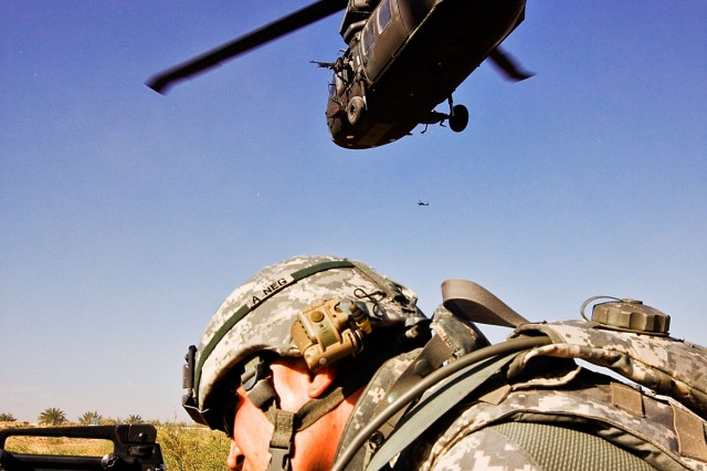 TAJI, Iraq-After air assaulting into a landing zone, Spc. Khalid Hermez, from Detroit, pulls security as a UH-60 Black Hawk helicopter departs the landing zone. U.S. Soldiers from the 1st Air Cavalry Brigade and the 34th Iraqi Army Brigade performed a joint air assault mission and patrol to check on living conditions of a small village north of here, Nov. 12.