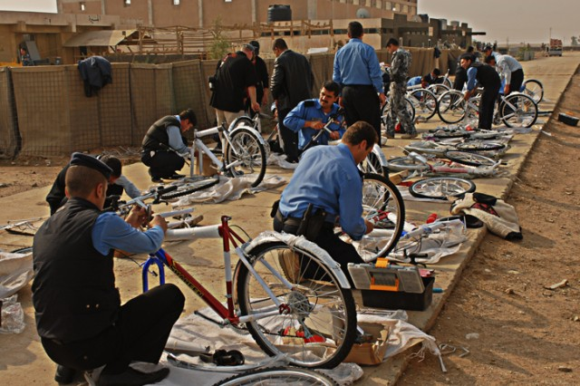 Iraqi Police work in groups and individually to assemble their bicycles during training at the Kirkuk Police Academy in Kirkuk, Iraq, Nov. 15. This group will be the first to graduate and become bicycle police officers in Kirkuk city.
