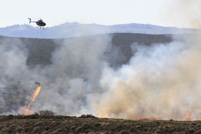 One of the contract helicopters lays a stream of ignition fuel onto the vegetation to burn it.
