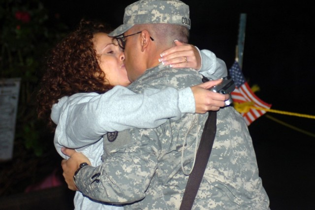 FORT DIX, N.J. - Sgt. Israel Colon from the 430th Transportation Company embraces his wife outside the Bravo Company Chapel here after running off the airport shuttle at a demobilization ceremony here 2 a.m. Oct. 18. Colon had been on a year-long deployment to Shank, Afghanistan.""