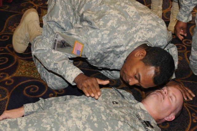 Master Sgt. Richard Archie, 100th Training Division, assesses a patient at the 68W combat medic sustainment training conference in Nashua, N.H.