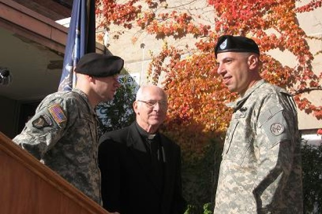 New York Army National Guard Capt. Richard Redmond and Sgt. Vincent Scalise of the 2nd Battalion, 108th Infantry Regiment speak with a priest on Veterans Day outside the Veteran's Center.