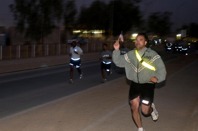 Soldiers and Airmen wave miniature American flags as they compete in the Veteran's Day 5K race Nov. 11 at Joint Base Balad, Iraq. The flags were donated by the Apollo Flag company in Totowa, N.J.