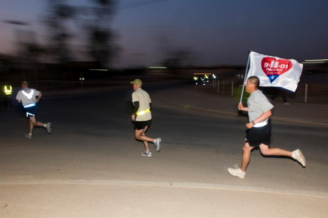 A Soldier carries a Sept. 11, 2001 remembrance flag, donated by the Apollo Flag company in Totowa, N.J., during the Veteran's Day 5K race Nov. 11 at Joint Base Balad, Iraq.