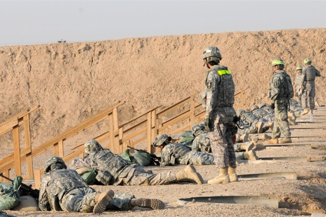 Range safety officers watch as Soldiers with the 36th Sustainment Brigade out of Temple, Texas, fire their weapons during a weapon qualification training exercise Nov. 10 at Lightning Memorial Range at Contingency Operating Location Adder, Iraq.