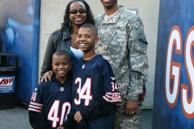 """1st. Lt. Drake Booker, 3rd Brigade, 75th Division (BCT), USAR from Chicago, IL, poses with his wife April and sons Devin, 10 and Jordan, 8 on the Chicago Bears sideline after being recognized as the """"Hero of the Game"""" during the 2009 Veterans Day observance at Soldier Field."""