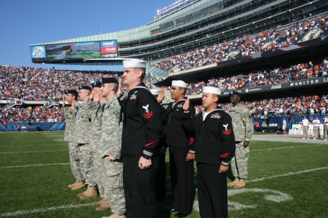 Ten service members from the Army, Navy and Air Force, re-enlist during half time at the Chicago Bears Veterans Day observance on Sunday, 08 November at Soldier Field, while over 65 Thousand screaming fans give them a standing ovation.  Brig. Gen. Joe Chesnut, who reenlisted the service members, is shown on the Jumbotron, while Master Sgt. Sheldrick 'Mac' McNeal stands behind his troops.