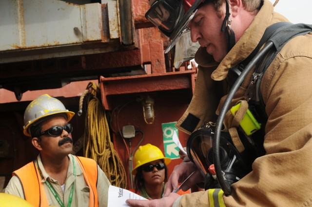 A fireman gets information from acting patients aboard the U.S chartered cargo ship MV AMERICAN TERN during a mass casualty training exercise held at Pier 17 at the Port of Shuaiba (SPOD) in Kuwait, Oct. 22.