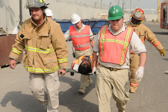 Fireman and responders transport a patient to a waiting Army ambulance after being evaluated during a mass casualty training exercise at Pier 17 at the Port of Shuaiba (SPOD) in Kuwait, Oct. 22.