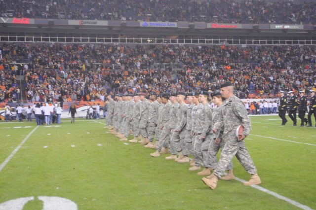DENVER-Fort Carson Soldiers march off the field at the end of halftime ceremonies with the souvenir game ball presented by the Denver Broncos. The Broncos saluted the military in a special ceremony Nov. 9.