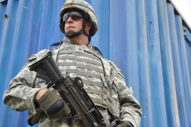 Pfc. Michael D. Johnson of Pell City, Ala., a military policeman with the 217th Military Police Co., stands guard during a mock village patrol exercise during his unitAca,!a,,cs deployment preparation at Fort Dix, N.J., July 16.