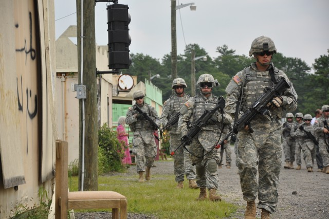 Members of the 217th Military Police Company perform a mock village patrol exercise during their unitAca,!a,,cs deployment preparation at Fort Dix, N.J., July 16.