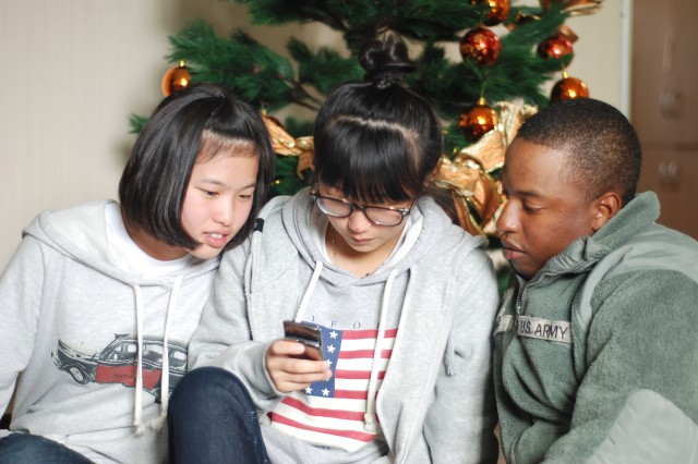 Pfc. Girard Whiting, (right) a Soldier assigned to 6-52 Air and Missile Defense Battalion in Suwon, Korea shared a moment with two orphans during his battalion\'s visit to the House that Dreams Develop orphanage.