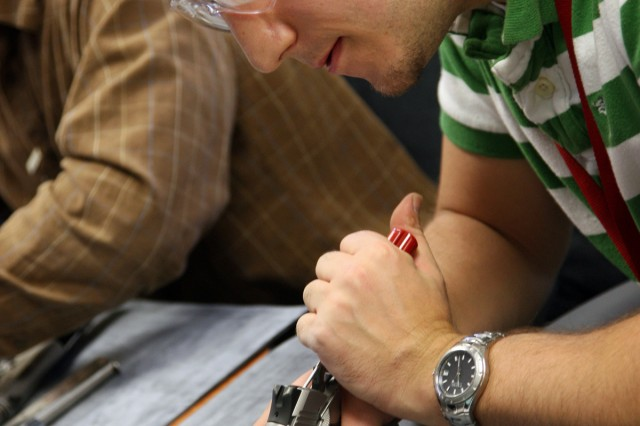A student takes apart a Kimber pistol during a Small Arms Design and Maintenance course.