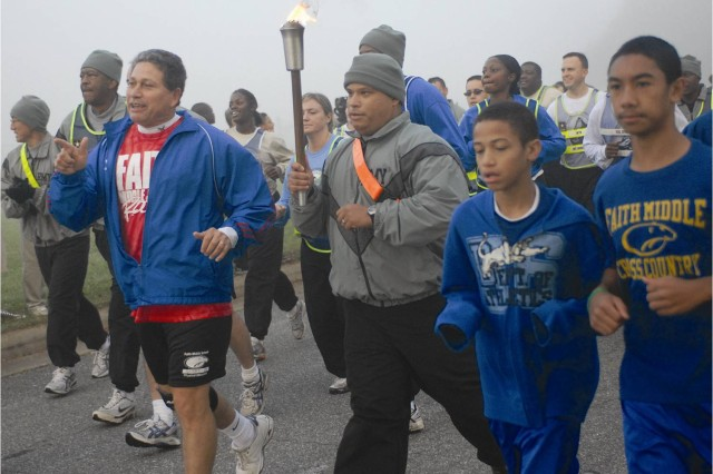 Staff Sgt. Victor Larronde, Warrior Transition Battalion, carries the Olympic torch by Faith Middle School students as Principal Julio Gonzalez (left) and a group of WTB Soldiers run with him. The Soldiers ran six miles carrying the torch.