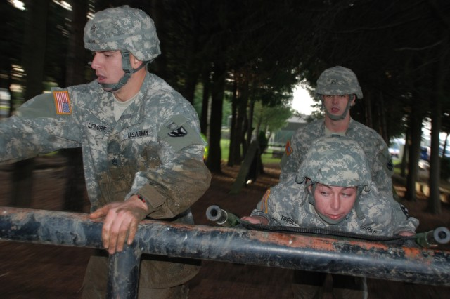 (Left to right) Staff Sgt. Christopher Lemine, Pfc. Amanda Tribble and Pfc. Tim Hocut, 511th Military Police Platoon, conquer the obstacle course to become the 14th Transportation Battalion Warrior Challenge winning team.