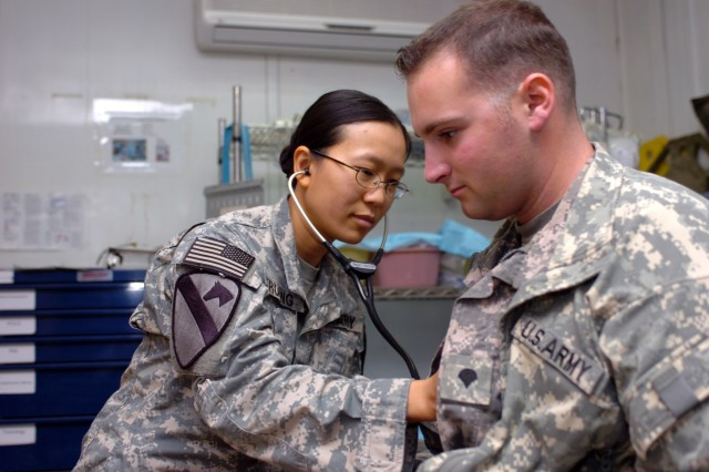 CAMP TAJI, Iraq-Capt. Tram Truong checks the heartbeat of Spc. Kevin Roberts, from Valley Center, Calif., during a routine medical examination at the 1st ACB Troop Medical Clinic, here.