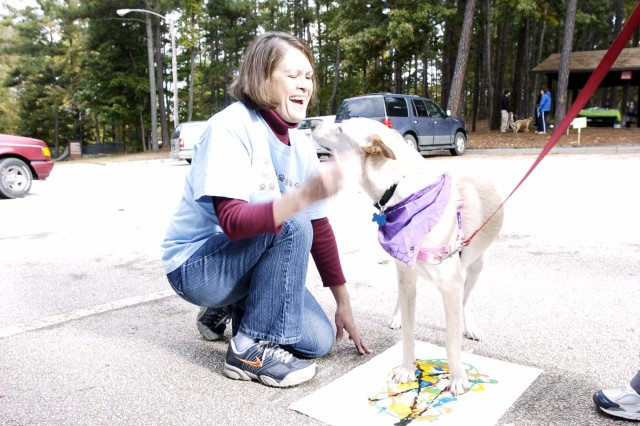 Evelyn White, a special security officer for G-2, U.S. Army Forces Command, gets some love and attention from Taffy Oct. 24 at the Peachtree City Dog Park during the Doggie Dash fundraiser for the Georgia Heartland Humane Society. White is a fundraiser and transporter for the organization, which helps find good homes for the animals.