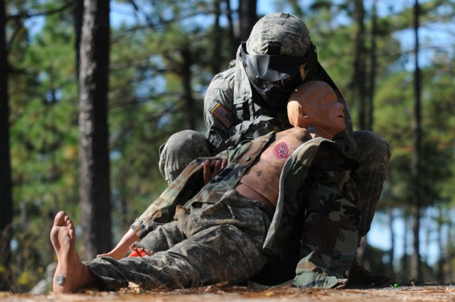 Spc. Joseph Weber, 108th Military Police Company, 16th MP Brigade, moves a dummy simulating an injured Soldier to safety during a lane training exercise Nov. 5. After taking cover, Weber treated the wounds using skills he learned during the combat lifesaver course