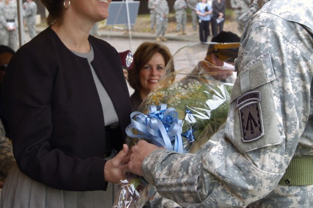 Melissa Helmick, wife of XVIII Airborne Corps' new commander, Lt. Gen. Frank G. Helmick, receives flowers during the XVIII Airborne Corps assumption of command ceremony Nov. 19 at Fort Bragg's main post parade field.