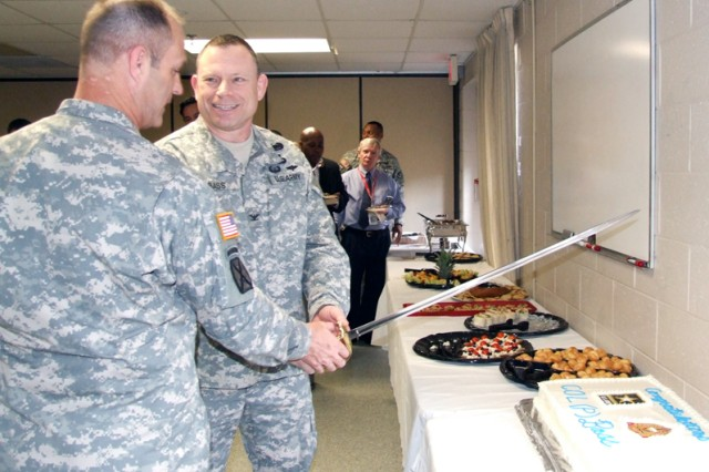 Command Sgt. Maj. John L. Murray watches as Col. (P) Joseph L. Bass as he proceeds to cut the cake at the Expeditionary Contracting Command change of command reception.