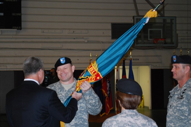 Col. (P) Joseph L. Bass receives the Expeditionary Contracting Command colors from Jeffrey Parsons, Army Contracting Command executive director, during the change of command ceremony.