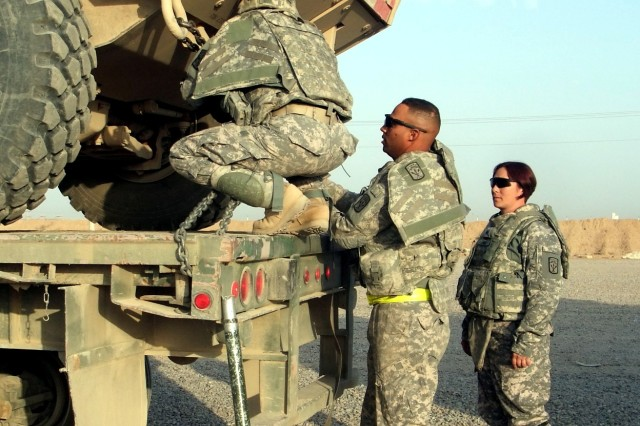 CONTINGENCY OPERATING LOCATION Q-WEST, Iraq - Sgt. Asia Thompson (left), of Lawrenceburg, N.C., and Spec. Steven Thompson, of Tarrytown, New York, inspect the tie-down of an Armored Security Vehicle under the watchful eye of Sgt. Denise Labo, Olalla, Wash., in the Q-West Convoy Support Center yard Nov. 9. They were among the Soldiers of the 40th Transportation Company, out of Fort Lewis, Wash., who hauled vehicles and equipment to COB Speicher in a convoy secured by Mississippi Guardsmen from A Company, 198th Combined Arms, a Hernando, Miss., unit that serves as the Q-West force protection company.