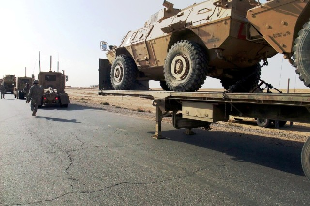 """CONTINGENCY OPERATING LOCATION Q-WEST, Iraq - Soldiers with the 40th Transportation Company, out of Fort Lewis, Wash., and Guardsmen with A Company, 2nd Battalion, 198th Combined Arms, headquartered in Hernando, Miss., hurry to switch out an overheated semi-truck during a Nov. 9 convoy mission from COB Q-West to COB Speicher. The Mississippians serve as Q-West's force protection company, and this marked their first convoy security mission."""""""
