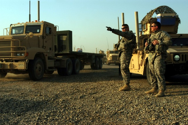 CONTINGENCY OPERATING LOCATION Q-WEST, Iraq -2nd Lt. Jeffery T. Watkins, a native of Biloxi, Miss., and Sgt. Brandon A. Craddock, Guardsmen with A Company, 2nd Battalion, 198th Combined Arms out of Hernando, Miss., direct trucks with the 40th Transportation Company, out of Fort Lewis, Wash., to a staging area at COB Speicher before a return trip to COB Q-West after offloading excess vehicles and equipment Nov. 9. The A Company Soldiers, who serve as Q-West's force protection company, provided security for the mission.""