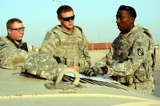 """CONTINGENCY OPERATING LOCATION Q-WEST, Iraq - Pfc. David G. Justus, a driver from Southaven, Miss., and Spec. Jason R. Brotherton, a gunner from Byhalia, Miss., listen as Sgt. Dreamus Harron, a vehicle commander from Brookhaven, Miss., briefs them before leaving COB Speicher to return to Q-West during a Nov. 9 convoy mission. All three are members of A Company, 2nd Battalion, 198th Combined Arms out of Hernando, Miss., Q-West's force protection company."""""""