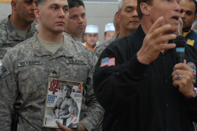 A Soldier holds a magazine bearing a photo of California Gov. Arnold Schwarzenegger, while the governor spoke to a packed chow hall at Camp Victory in Baghdad, Nov. 16. Schwarzenegger said he came back to Iraq to keep a promise he made to troops in 2003, and to thank Servicemembers for their dedication to the mission here in Iraq.