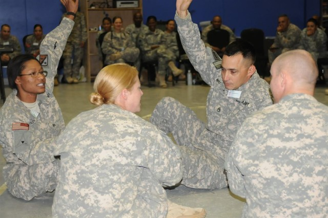 Soldiers at the Equal Opportunity Leaders Course, which ran Nov. 14 though Nov. 21, raise their hands to vote another Soldier off of the boat, during a scenario at Morale, Welfare and Recreation Center east at Joint Base Balad, Iraq. The Soldiers were given real-life scenarios to help them understand the prevalence of discrimination.