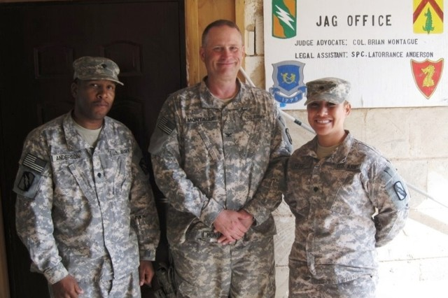 CONTINGENCY OPERATING LOCATION Q-WEST, Iraq - Spc. Latorrance Anderson (left) of Tunica, Miss., Col. Brian A. Montague, of Hattiesburg, Miss., and Spc. Tamaleilua Mose, of Chaney, Wash., in an Aug. 8 photo, standing in front of a newly painted sign for the Judge Advocate General office. Montague, command judge advocate for Mississippi's 2nd Battalion, 198th Combined Arms out of Senatobia, Miss., received a Meritorious Service Medal in a Nov. 13 ceremony outside the base defense operations center, Contingency Operating Location Q-West, Iraq.