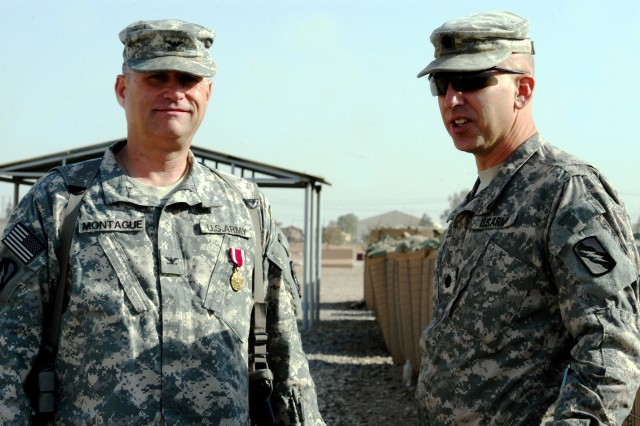 CONTINGENCY OPERATING LOCATION Q-WEST, Iraq - After being awarded a Meritorious Service Medal, Col. Brian A. Montague (left), a native of Hattiesburg, Miss., and command judge advocate for Mississippi's 2nd Battalion, 198th Combined Arms out of Senatobia, Miss., chats with Lt. Col. Kerry Goodman, a native of Meridian, Miss., and commander of 2/198th CAB during a Nov. 13 ceremony outside the base defense operations center, Contingency Operating Location Q-West, Iraq. Montague, Mississippi's senior Army JAG, volunteered to deploy with the 155th Heavy Brigade Combat Team and serves as JAG for two battalions, the 2/198th CAB at Q-West and the 2nd Battalion, 114th Field Artillery Regiment at Contingency Operating Station Marez.