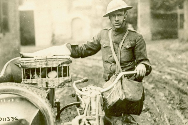 """Underway and Under Fire! : This image is captioned """"Motorcycle despatch Rider starting under heavy shell fire to deliver pigeons to our most advanced position. France."""" (WWI Signal Corps Photograph Collection)."""