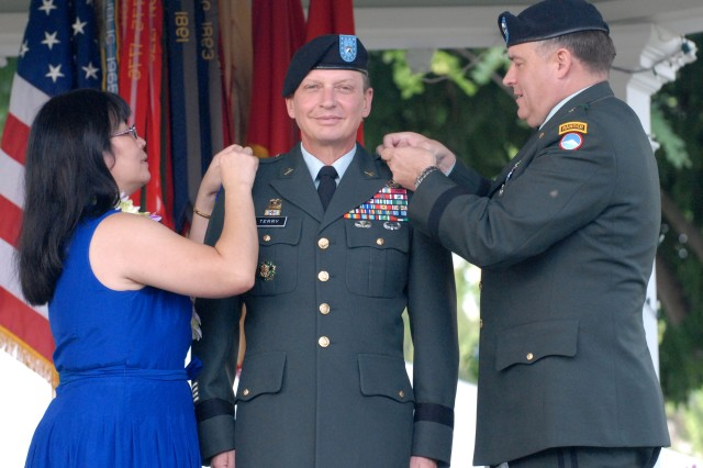 Cathy Terry, left, and Maj. Gen. Frank Wiercinski, commanding general, U.S. Army, Japan, pin the stars on Maj. Gen. Michael J. Terry, commanding general, 8th Theater Sustainment Command, as he stands at attention during a promotion ceremony held on Fort Shafter, Hawaii, Nov. 16.
